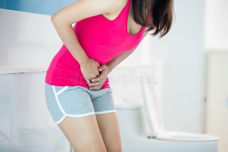 Kvinnan känner sig smärtar med diarré royaltyfria foton