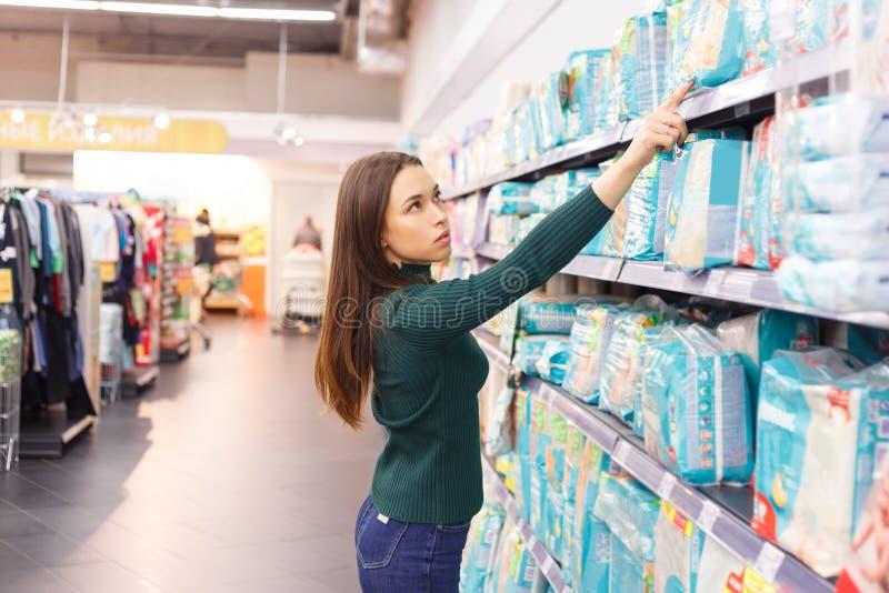 Kvinnan köper blöjor på supermarket, stående av den unga lyckliga modern shoppar in gallerian royaltyfri bild
