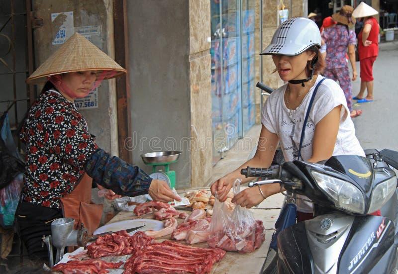 Kvinnan köper några stycken av kött royaltyfri bild
