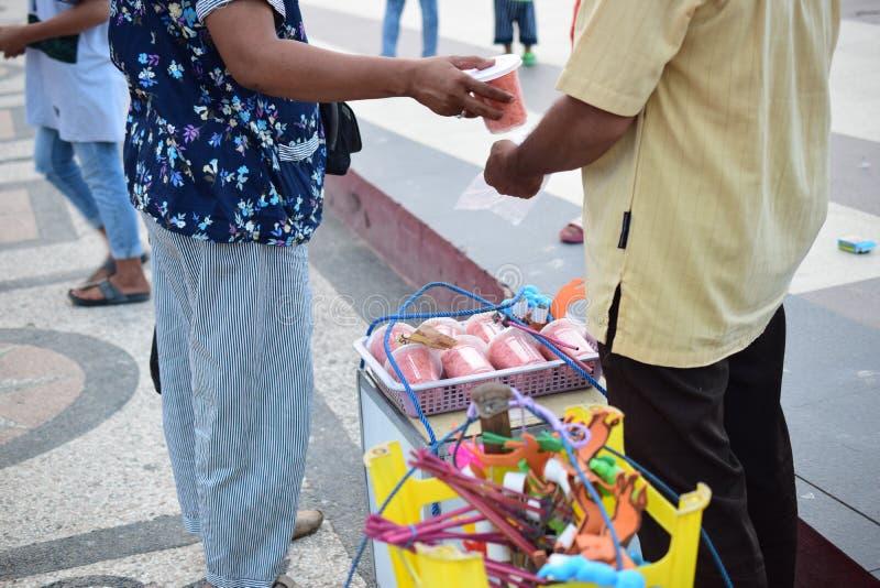 Kvinnan köper sockervadden till en traditionell säljare royaltyfria foton