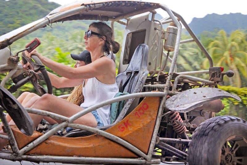 Kvinnan kör en barnvagn på ett safariaffärsföretag turnerar i den Rarotonga kuttrandet arkivfoto