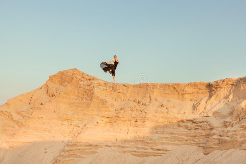 Kvinnan kör ner lutningen av sanddyn royaltyfri foto