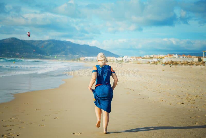 Kvinnan kör på den sandiga stranden royaltyfria bilder