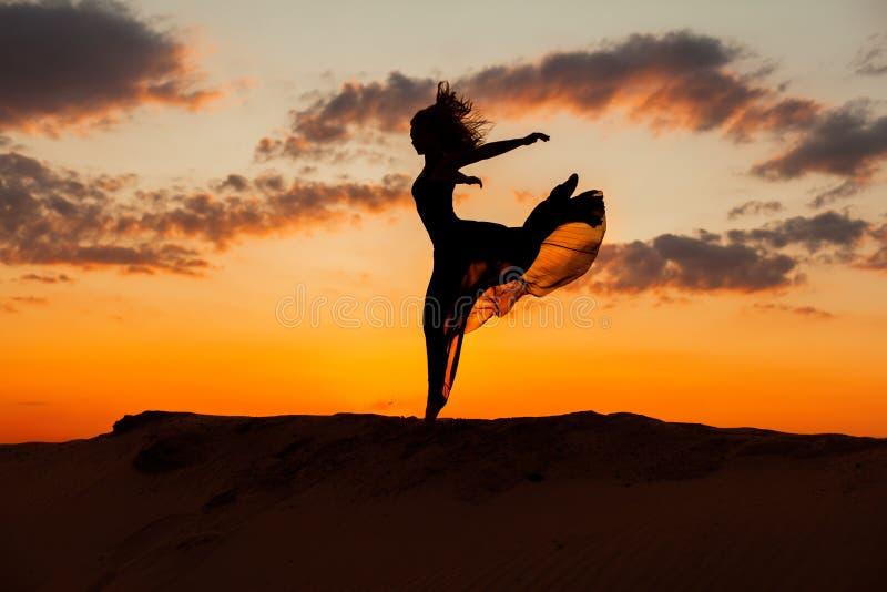 Kvinnan kör på solnedgången arkivbilder