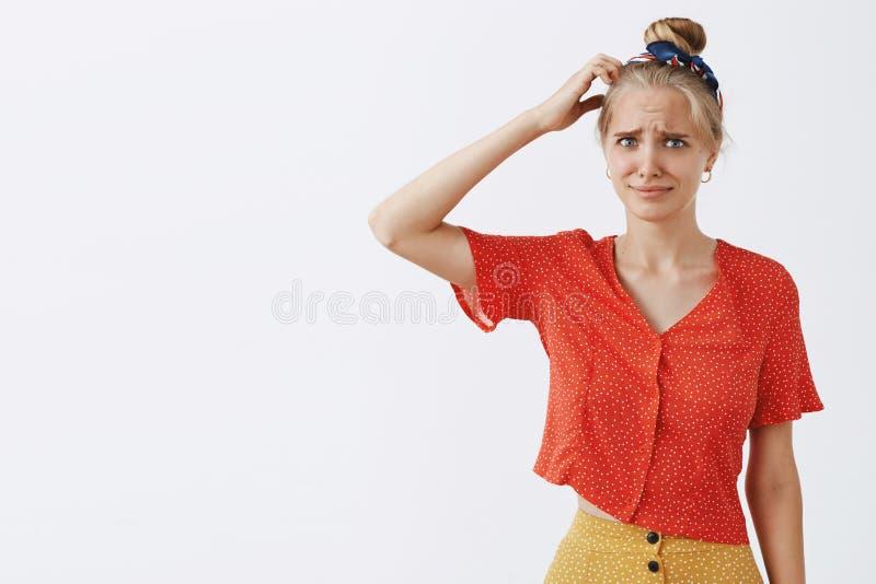 Kvinnan kan inte få skämtet som står det korkade och förvirrade skrapande huvudet och att stirra som oroas och angås på kameran royaltyfri fotografi