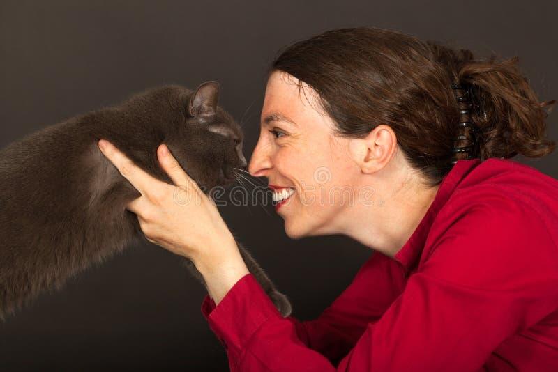 Kvinnan kelar med hennes katt royaltyfri bild