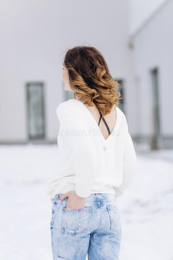 Kvinnan klädde stylishly vinter för jeanströjasnö royaltyfria foton