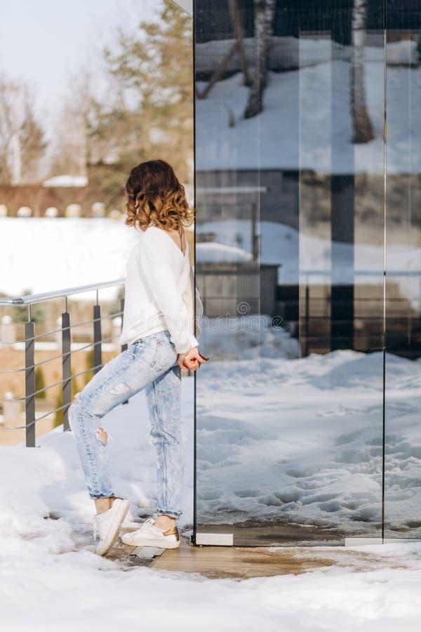 Kvinnan klädde stylishly vinter för jeanströjasnö fotografering för bildbyråer