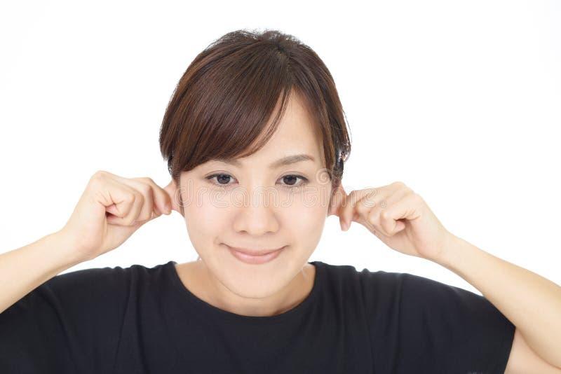 Kvinnan klämmer hennes öron arkivbild