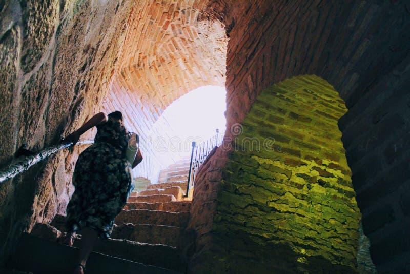Kvinnan klättrar den branta trappan inom det röda tornet - den huvudsakliga befästningen av staden Alanya, Turkiet royaltyfri foto