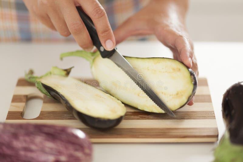 Kvinnan klipper aubergine på skärbräda i kök arkivbild