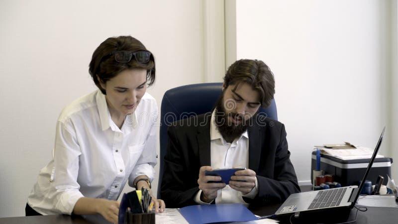 Kvinnan kontorsarbetare visar viktiga dokument till hennes skäggiga framstickande som är upptaget med att spela smarta telefonlek royaltyfri fotografi