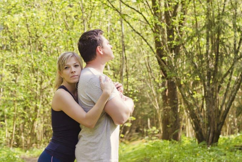 Kvinnan kramar en man som står med henne tillbaka till henne Begreppet av familjproblem, förlåtelse royaltyfri fotografi