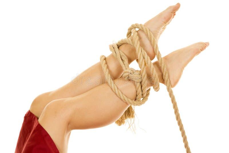 Kvinnan lägger benen på ryggen med det röda arket som binds med repfot upp arkivbild