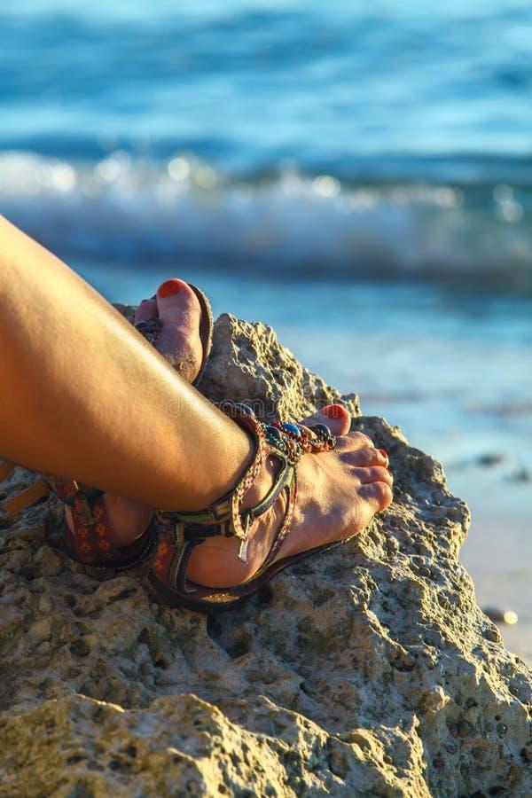 Kvinnan lägger benen på ryggen med sandaler på stenen nära tropisk blå havsFilippinerna royaltyfri bild