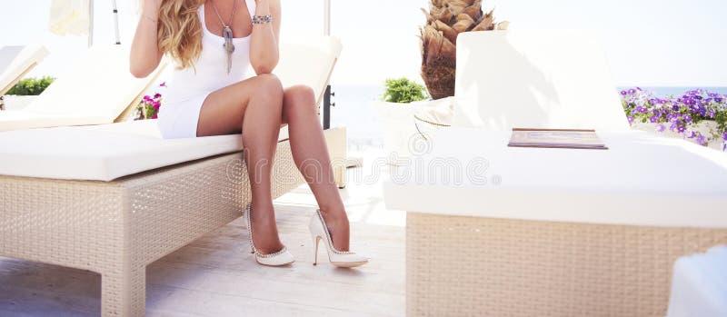 Kvinnan lägger benen på ryggen på en soldagdrivare på en strand arkivfoton
