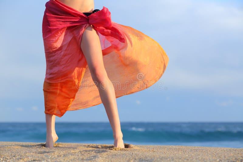 Kvinnan lägger benen på ryggen på semestrar som poserar på stranden med en pareo arkivfoto