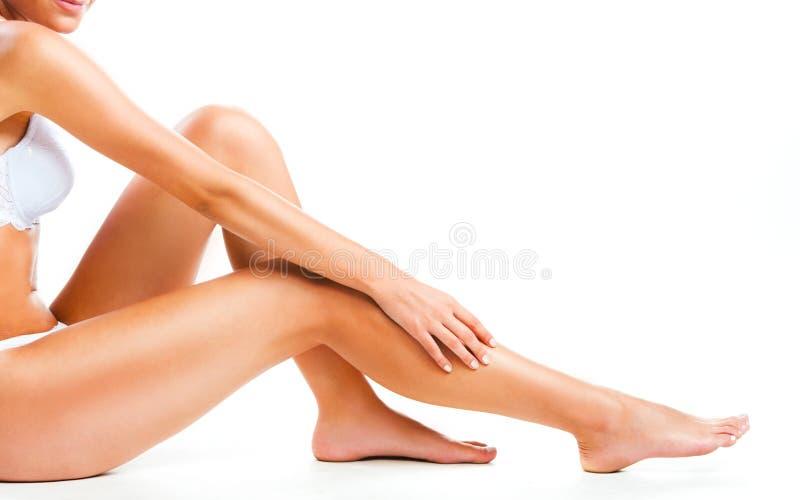 Kvinnan lägger benen på ryggen på vit arkivbild