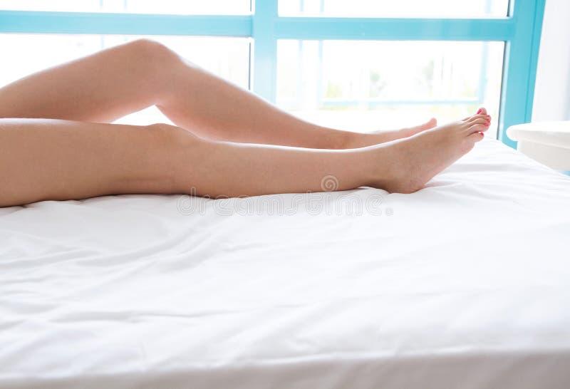 Kvinnan lägger benen på ryggen på sängen i vit sängkläder mot en ljus fönsterbakgrund, skönhetlivsstilbegrepp royaltyfri fotografi