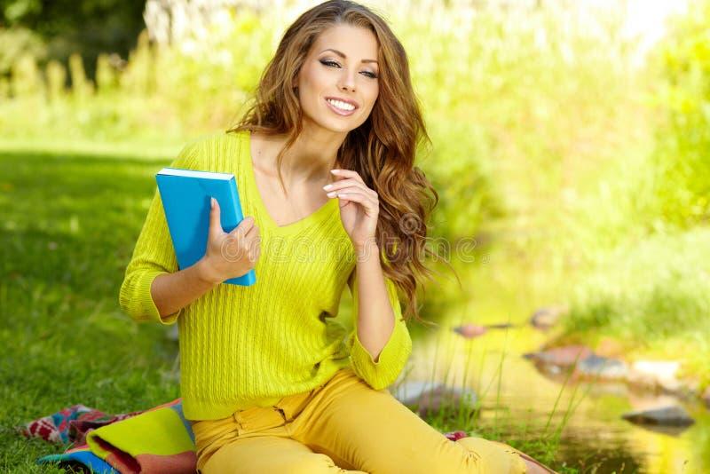 Kvinnan lägger på grönt fält och läser boken. arkivbild