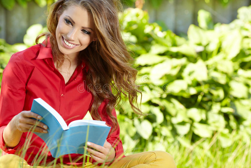 Kvinnan lägger på grönt fält och läser boken. arkivfoto