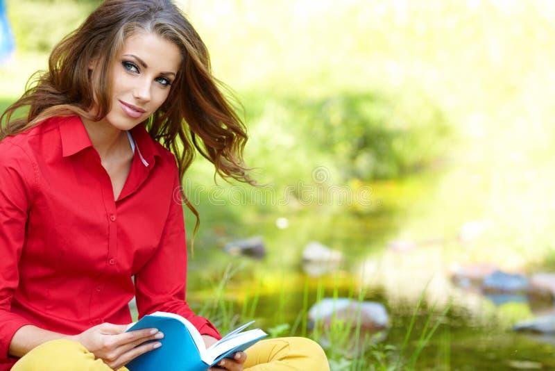 Kvinnan lägger på grönt fält och läser boken. royaltyfri fotografi