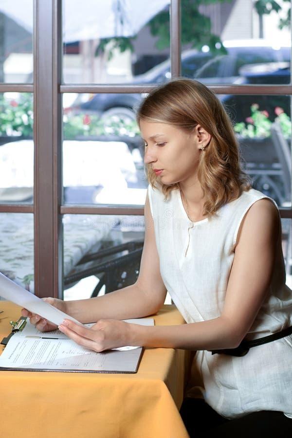 Kvinnan läser dokument som sitter nära fönstret royaltyfri foto