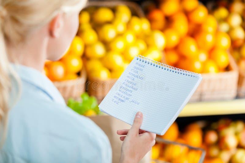 Kvinnan läser shoppinglistan nära bunten av frukter arkivbild