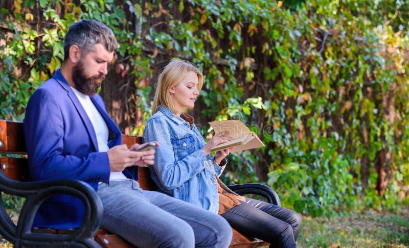 Kvinnan läste boken, medan mannen läste ebooksmartphonen Mannen med skägget och kvinnan läste alternativ informationslagring avlä arkivbilder