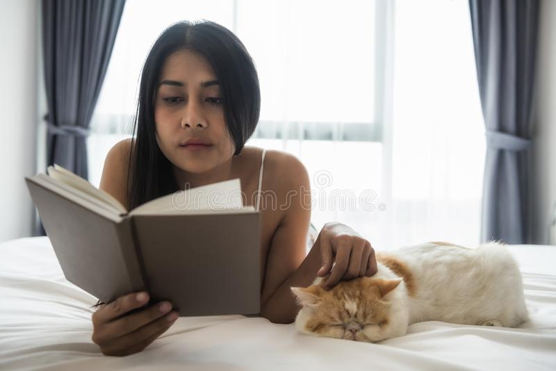 kvinnan läste boken och lekkatten på säng royaltyfria foton