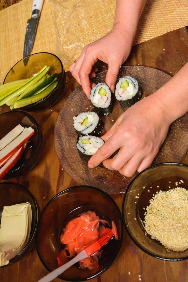 Kvinnan lagade mat sushi och f?rlade dem p? en rund platta royaltyfri bild
