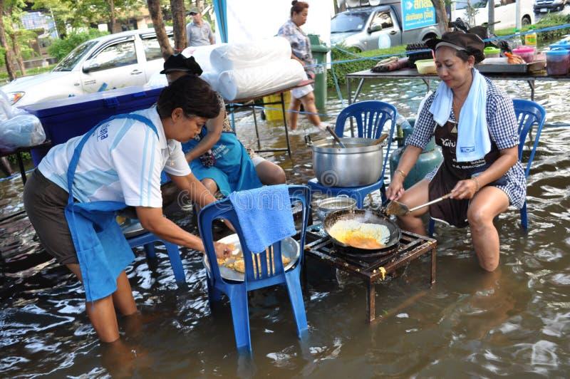 Kvinnan lagar mat fria mål för flyktingar i en översvämmad gata av Bangkok, Thailand, på 31 Oktober 2011 royaltyfri foto