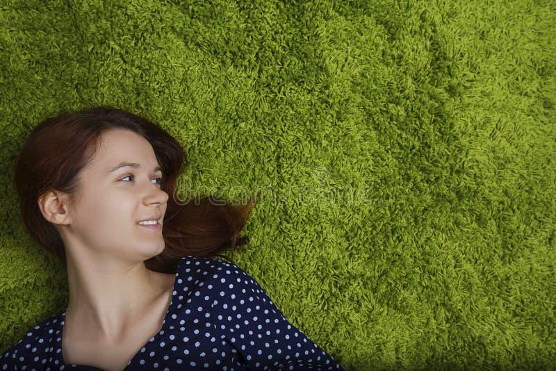 Kvinnan ler känsligt lyckligt ligga ner på grönt konstgjort gräs arkivbild