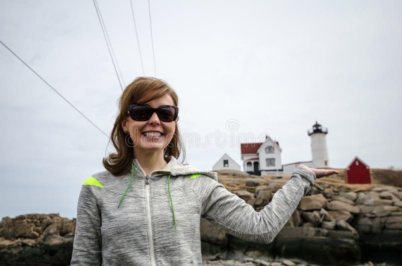 Kvinnan ler och rymmer Nubblefyren i en tvungen perspektivsikt royaltyfri bild