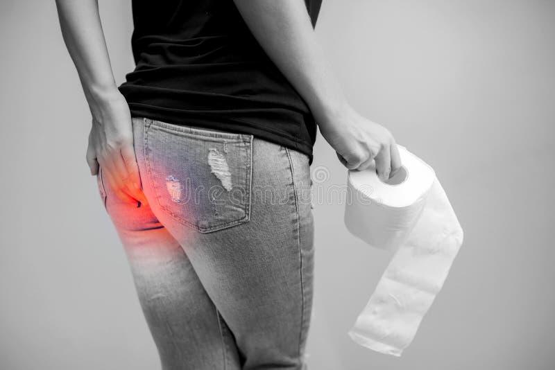 Kvinnan lider från diarré rymmer rulle för toalettpapper Magen ups royaltyfria bilder
