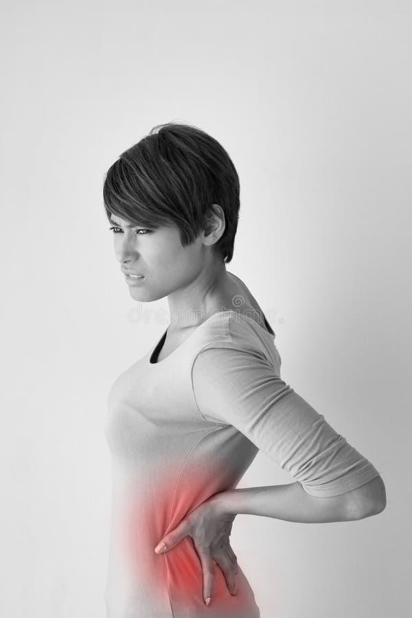 Kvinnan lider från tillbaka smärtar, begreppet av kontorssyndrommen arkivbilder