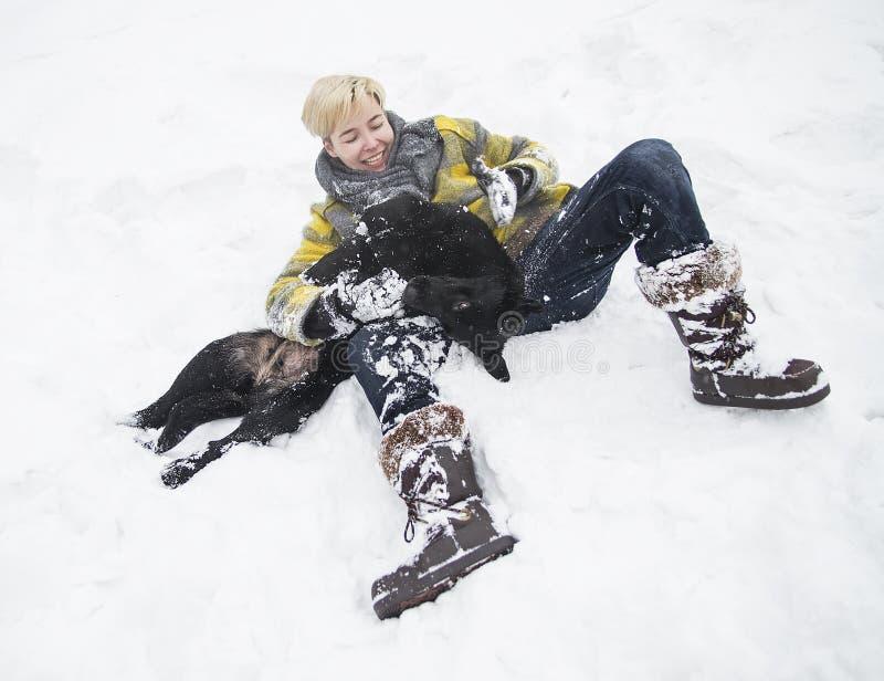 Kvinnan ligger i snön med en svart hund royaltyfri bild