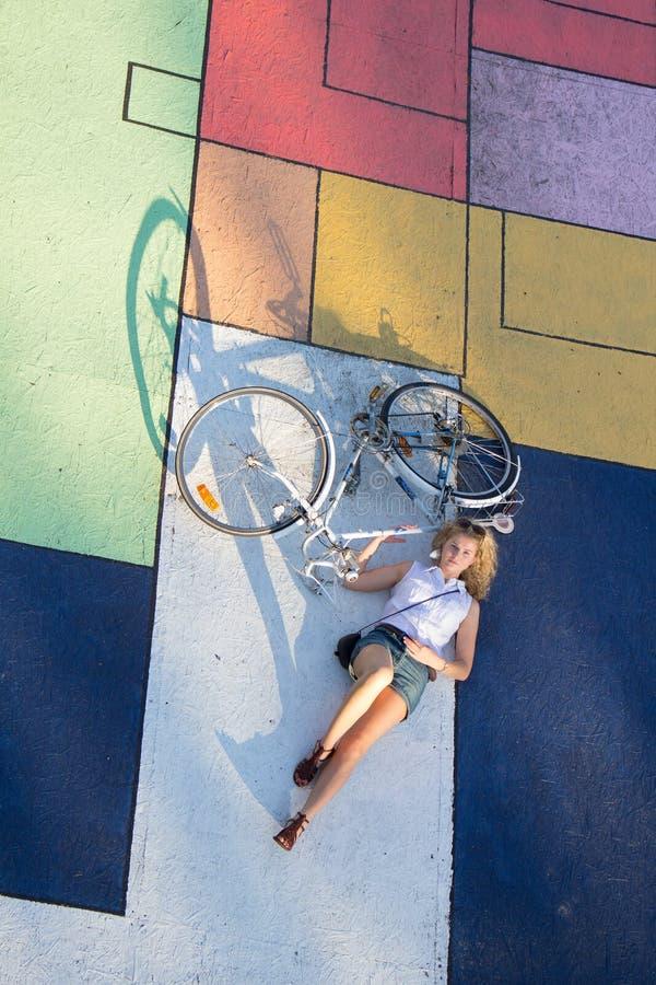 Kvinnan ligger på baksida med hennes retro cykel royaltyfri bild