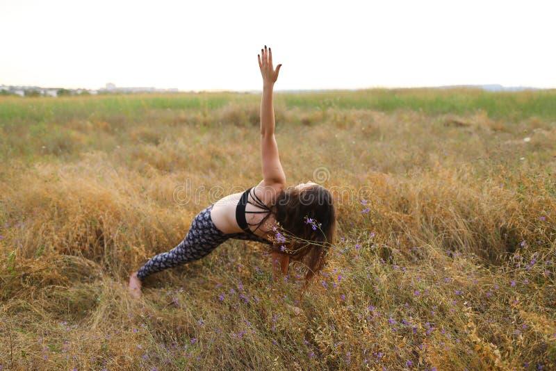 Kvinnan lutade framåtriktat och vände kroppen som litet inhyser till sidan, nolla royaltyfri fotografi