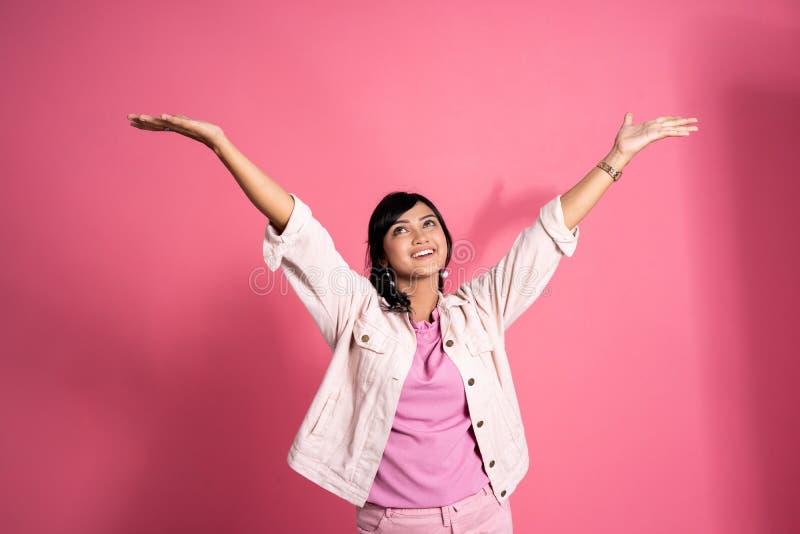 Kvinnan lyftte armen lyckligt ?ver rosa bakgrund arkivfoton