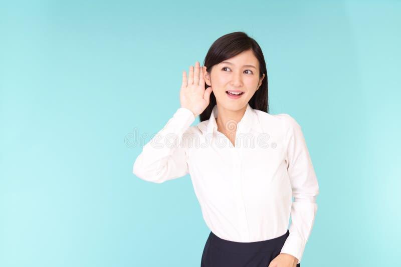Kvinnan lyssnar försiktigt arkivfoto