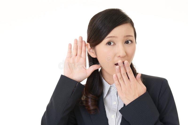 Kvinnan lyssnar försiktigt arkivbild