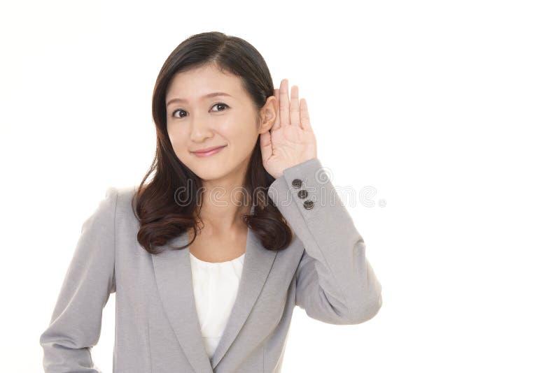 Kvinnan lyssnar f?rsiktigt royaltyfri foto