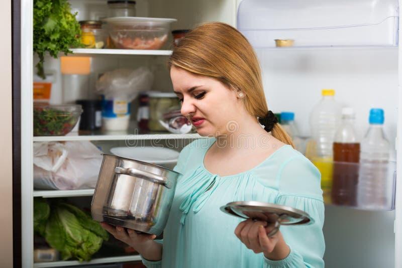 Kvinnan märkte den illaluktande lukten av mat från eldfasta formen arkivbilder