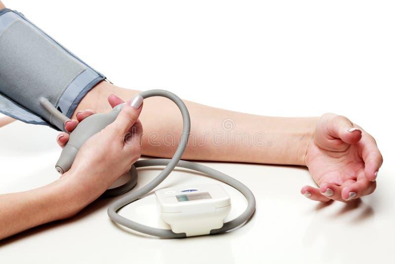 Kvinnan mäter hennes blodtryck royaltyfri fotografi