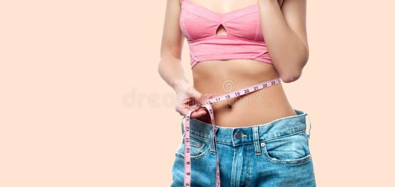 Kvinnan mäter midjan efter viktförlust på urblekt pastellfärgad bakgrund arkivbilder