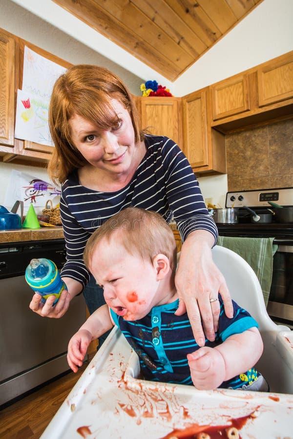 Kvinnan matar hennes Gumpy behandla som ett barn royaltyfri bild