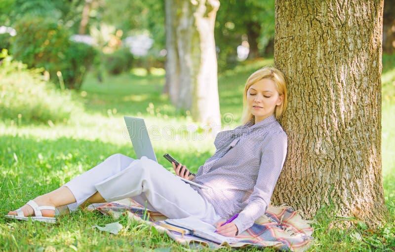 Kvinnan med arbete f?r b?rbar datordatoren lutar utomhus p? tr?dstammen Flickaarbete med b?rbara datorn i att parkera f?r att sit royaltyfria bilder