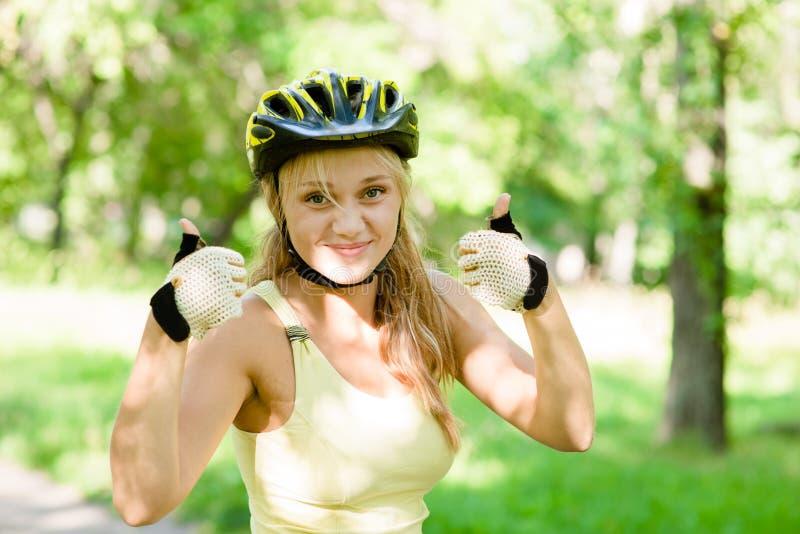 Kvinnan med att cykla hjälmvisning tummar upp arkivbild