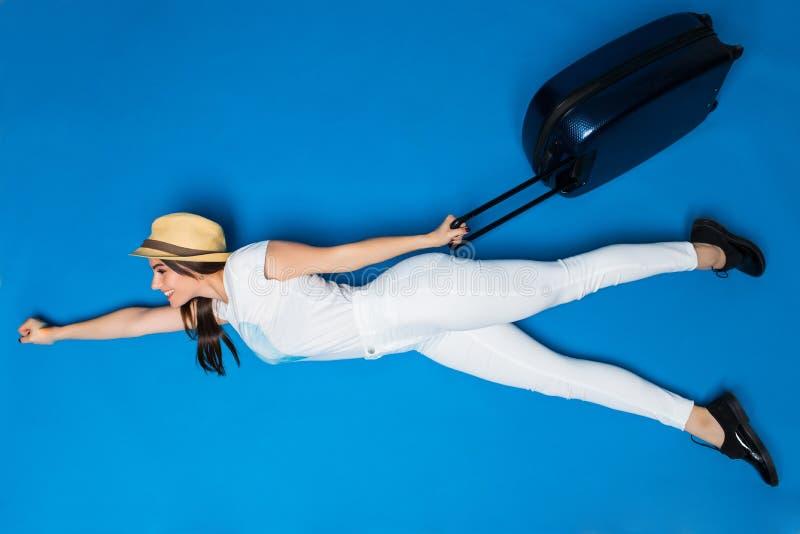 Kvinnan med bagage i händer flyger till det nya loppet på blå bakgrund Kvinnafluga till den nya plana turen nytt affärsföretag royaltyfria foton